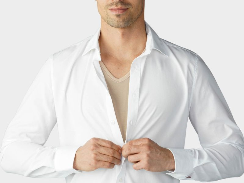 man wearing tan undershirt under white dress shirt