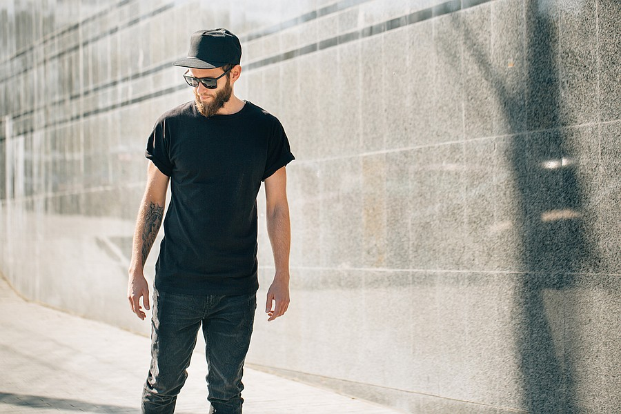 black tee with undershirt – Bearded man with sunglasses and hat wearing a black tee- shirt with an undershirt.