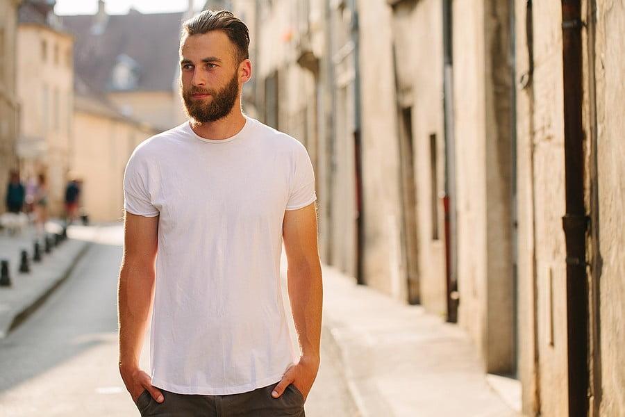Man wearing undershirt under teeshirt – Man standing in narrow street wearing a white t-shirt with an undershirt underneath